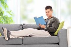 Het jonge kerel ontspannen met een boek thuis Stock Afbeelding
