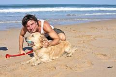 Het jonge kerel spelen met zijn hond Royalty-vrije Stock Afbeelding