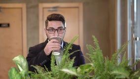 Het jonge kerelbrunette in glazen drinkt koffie stock footage
