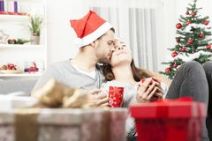Het jonge Kerstmispaar ontspannen op bank Stock Afbeeldingen
