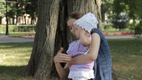 Het jonge kindermeisje wrijft haar ogen terwijl het hebben van een babymeisje in haar overlapping stock footage