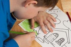 Het jonge Kleuren van de Jongen op Vloer Stock Fotografie