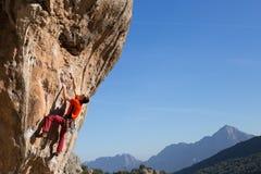 Het jonge klimmer hangen door een klip Royalty-vrije Stock Foto