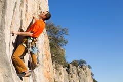 Het jonge klimmer hangen door een klip Stock Foto