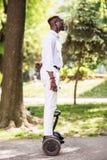 Het jonge knappe afro Amerikaanse mens drijven op segway in het park royalty-vrije stock fotografie