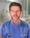 Het jonge knappe en zekere geneeskunde arts stellen vrolijk op blauw schrobt en stethoscoop op zijn hals glimlachend geïsoleerd g stock afbeelding