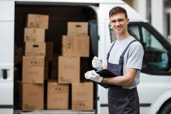 Het jonge knappe het glimlachen arbeider eenvormig dragen bevindt zich naast het bestelwagenhoogtepunt die van dozen een klembord royalty-vrije stock afbeeldingen