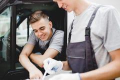 Het jonge knappe kerel eenvormig dragen richt op het klembord terwijl het zitten in de auto Een andere arbeider het dragen royalty-vrije stock afbeeldingen