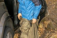 Het jonge knappe mannetje zette op waterdicht kostuum voor de jacht of visserij in de koele herfst dag B royalty-vrije stock foto's