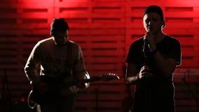 Het jonge knappe mens zingen met gitaarspeler stock footage