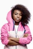 Het jonge krullende bruin-haired meisje van mod. gekleed in de roze blazer met een kap stelt bij de witte achtergrond in de studi stock fotografie