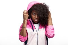 Het jonge krullende bruin-haired meisje van mod. gekleed in de roze blazer met een kap stelt bij de witte achtergrond in de studi royalty-vrije stock afbeelding