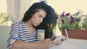 Het jonge krullende meisje typt een bericht op telefoon en ontspant bij de zomerterras stock footage