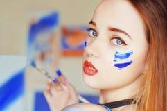 Het jonge kunstenaar schilderen Meisje die een beeld in huisstudio schilderen Model het schilderen borstel op schildersezel Sensu stock afbeelding