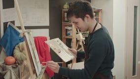 Het jonge kunstenaar schilderen met olieverven op canvas stock footage