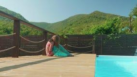Het jonge langharige blonde puft omhoog de matras door de pool stock videobeelden