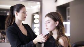 Het jonge langharige meisje zit als voorzitter vooraan de spiegel met gloeilampen, klaar voor de samenstellingsdienst in de salon stock videobeelden