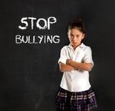 Het jonge Latijnse leuke die schoolmeisje deed schrikken en droevig en de woordeneinde intimidatietekst met krijt wordt geschreve royalty-vrije stock foto
