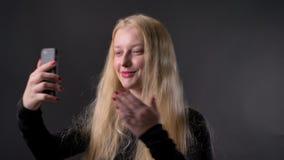 Het jonge leuke blonde meisje met roze lippenstift heeft een videovraag op smartphone, communicatie concept, grijze achtergrond stock footage
