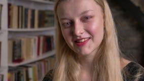 Het jonge leuke blonde meisje met roze lippenstift let op bij camera, het glimlachen, bibliotheek op achtergrond, vage achtergron stock footage