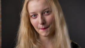 Het jonge leuke blonde meisje met roze lippenstift let op bij camera, het glimlachen, grijze achtergrond stock videobeelden