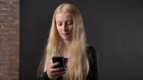 Het jonge leuke blonde meisje met roze lippenstift typt bericht op smartphone, communicatie concept, gery achtergrond stock video