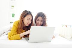 Het jonge leuke lesbische paar die van Azië laptop met geluk met behulp van bij ho Royalty-vrije Stock Fotografie