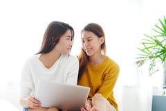 Het jonge leuke lesbische paar die van Azië laptop met geluk met behulp van bij ho Stock Foto's