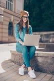 Het jonge leuke meisje blogger werkt in openlucht aan haar laptop Zij I royalty-vrije stock fotografie