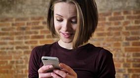 Het jonge leuke meisje leest bericht op haar smartphone, is zij verrast, communicatie concept, baksteenachtergrond stock footage