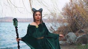 Het jonge leuke meisje met creatieve samenstelling stelt voor fotograaf door het meer, dame met grote zwarte hoornen op hoofd in  stock videobeelden
