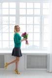 Het jonge leuke meisje met een boeket van de lente bloeit, blij, 8 Maart, de internationale vakantievrouwen ' S Stock Afbeelding