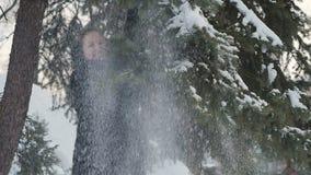 Het jonge leuke meisje schudt een sneeuwsparrentakken stock videobeelden