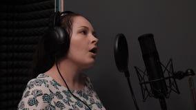 Het jonge leuke meisje zingt emotioneel operalied Aantrekkelijke vrouw bij vocale opnamestudio Opname van lied Pop vrouwelijke ar stock video