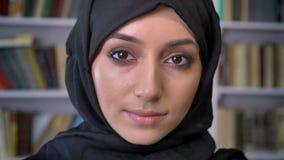 Het jonge leuke moslimmeisje in hijab let op bij camera, neer lettend op in boek, godsdienstig concept, boekenrek op achtergrond