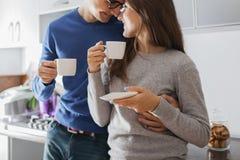 Het jonge leuke paar koesteren en het drinken thee in de keuken royalty-vrije stock fotografie