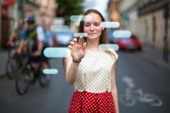 Het jonge leuke tienermeisje in de straat drukt een denkbeeldige knoop in de lucht Royalty-vrije Stock Foto