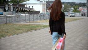 Het jonge magere brunette gaat rond de stad stock footage