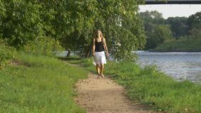 Het jonge magere meisje gaat op een voetpad in het bos stock video