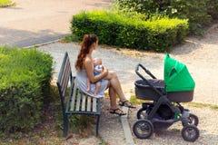 Het jonge mamma de borst geven buiten op de parkbank, einde tijdens gang met de kinderwagen, wijfje houdt haar baby royalty-vrije stock afbeeldingen