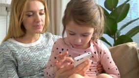 Het jonge mamma en haar dochter spelen een smartphone en glimlachen terwijl thuis het zitten op bank Langzame Motie stock video