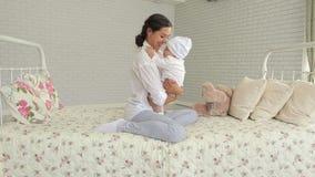 Het jonge mamma spelen met haar pasgeboren zoon Kind en ouder samen thuis stock video