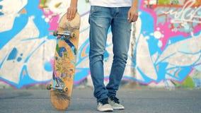 Het jonge man been heft een skateboard op terwijl status naast een graffitimuur stock videobeelden