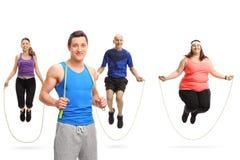Het jonge mannelijke atleet stellen met een touwtjespringen en een groep die mensen met een touwtjespringen springen royalty-vrije stock foto's