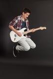 Het jonge mannelijke springen met gitaar Royalty-vrije Stock Foto's