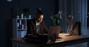 Het jonge mannelijke uitvoerende werken aan laptop laat bij nacht stock videobeelden
