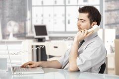 Het jonge mannelijke werken in bureau dat aan telefoon spreekt Stock Foto's