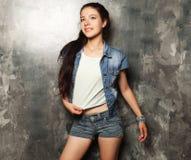 Het jonge mannequin stellen in studio, grijze achtergrond Stock Foto's