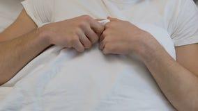 Het jonge mannetje die in bed liggen deed schrikken, gebrek aan seksuele opvoeding, ongemakkelijk ogenblik stock footage