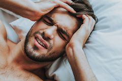 Het jonge mannetje lag in bed met vreselijke hoofdpijn royalty-vrije stock foto